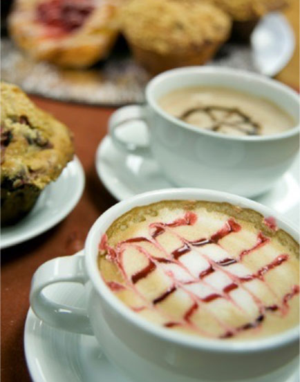 Specialty cups of coffee and a plate of muffins and pastries
