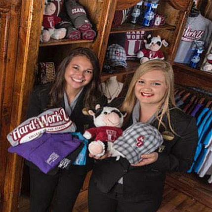 Two female student workers standing in the Keeter Center gift shop holding store merchandise.